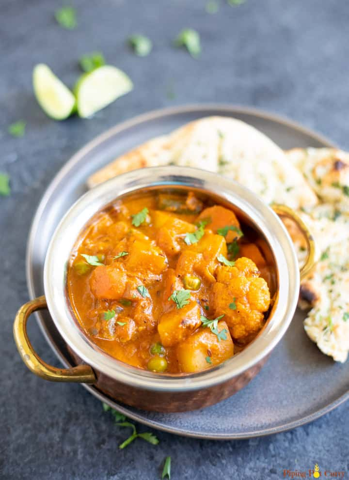 Vegetable Korma Curry in a bowl with naan on the side