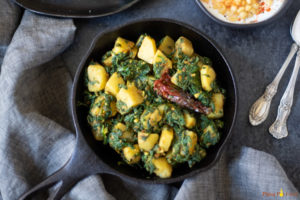 Spinach and potato stir fry in a cast iron pan