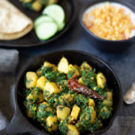Aloo Palak (Potatoes & Spinach Stir Fry) in a cast iron skillet with raita and roti