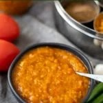 Indian curry sauce made with onions and tomatoes in a black bowl with spices and tomatoes in the back