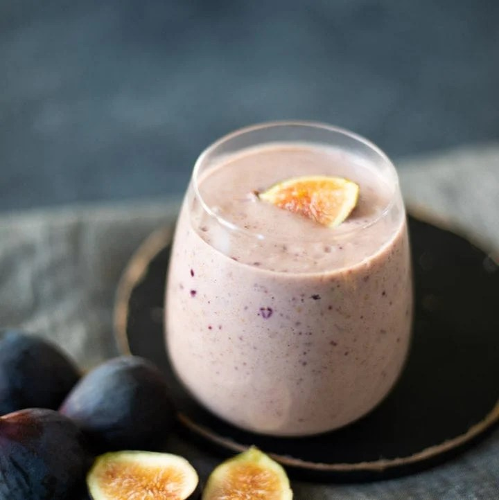 Fig smoothie with some figs lying beside the glass