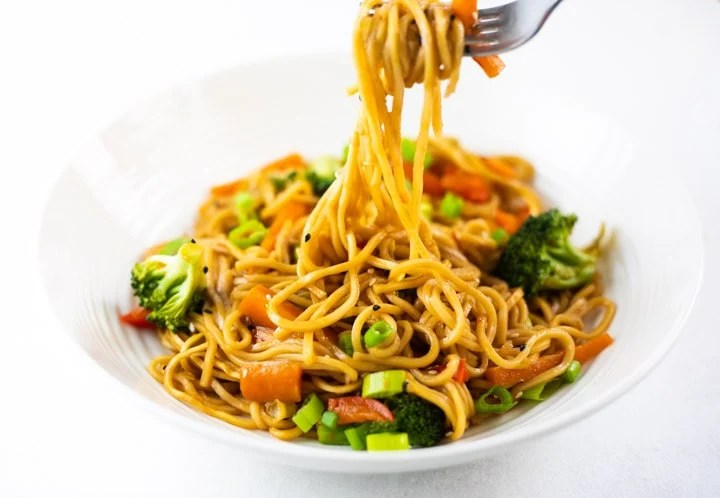 Lo Mein noodles with vegetables in a white bowl and being picked by fork