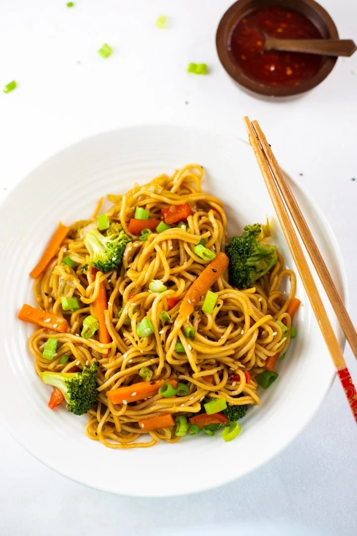 vegetable lo mein on a white plate with chopsticks and a side dish of sauce