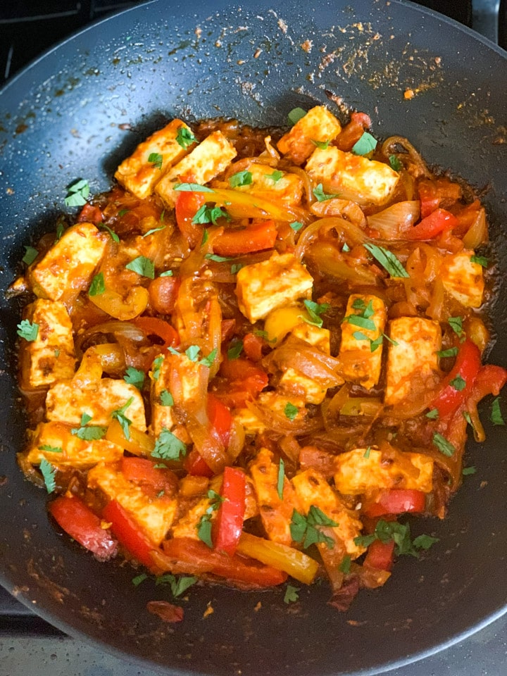 Paneer with onions and peppers in a pan garnished with cilantro