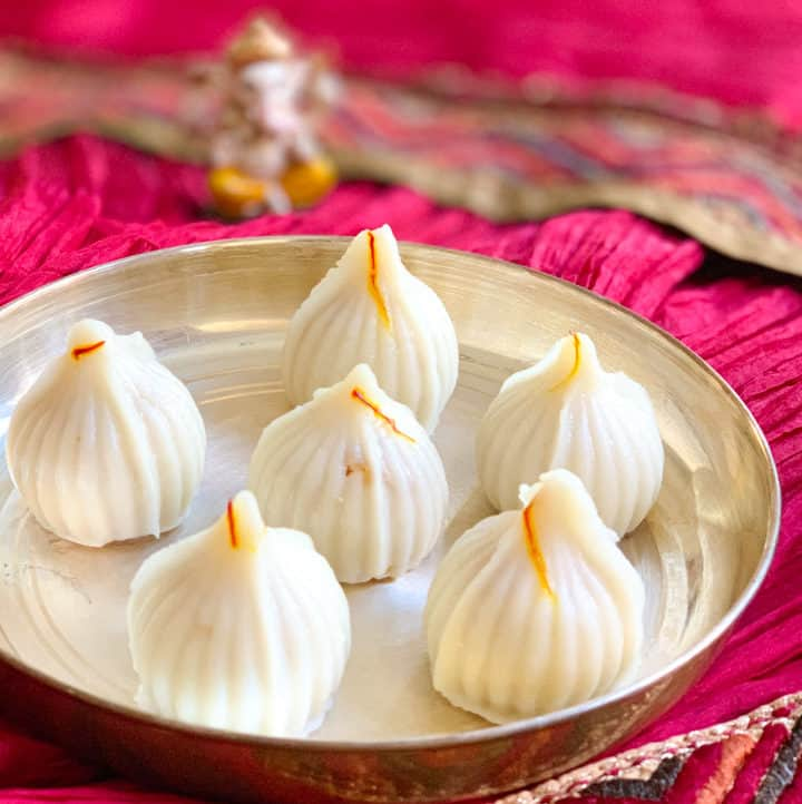 Ukadiche Modak (sweet rice dumplings) in a plate and lord Ganesha idol in the back
