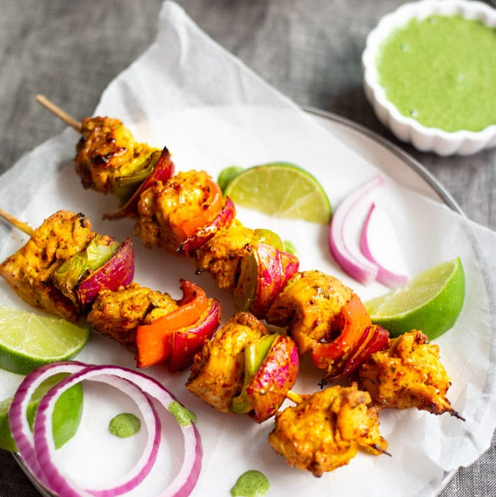 Chicken Tikka Kebab garnished with onions and green chutney on side