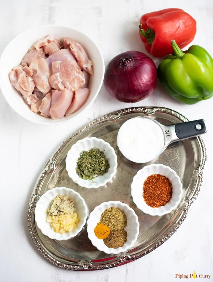 ingredients for chicken tikka kebabs including chicken pieces, veggies, and spices