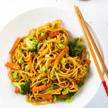Lo mein noodles in a white bowl with chopsticks and chili sauce on the side.