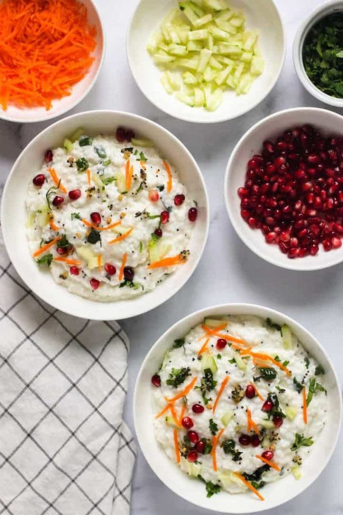 Yogurt rice garnished with pomegranate seeds served in two bowls