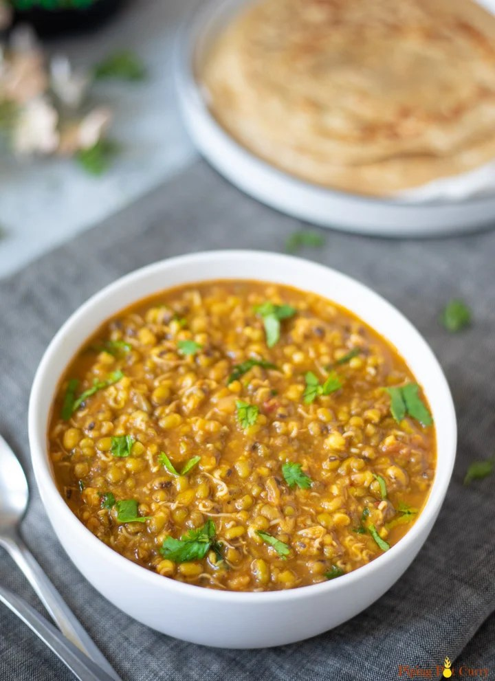 Moong Sprouts Curry in a whole bowl with parathas in a plate