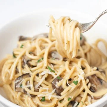 Spaghetti pasta with mushrooms in a fork and white bowl
