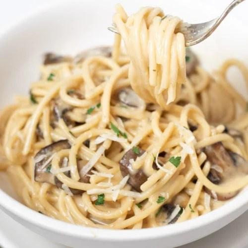 creamy mushroom spaghetti in a white bowl
