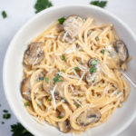 Creamy Spaghetti Pasta with mushrooms in a white bowl garnished with cheese and parsley
