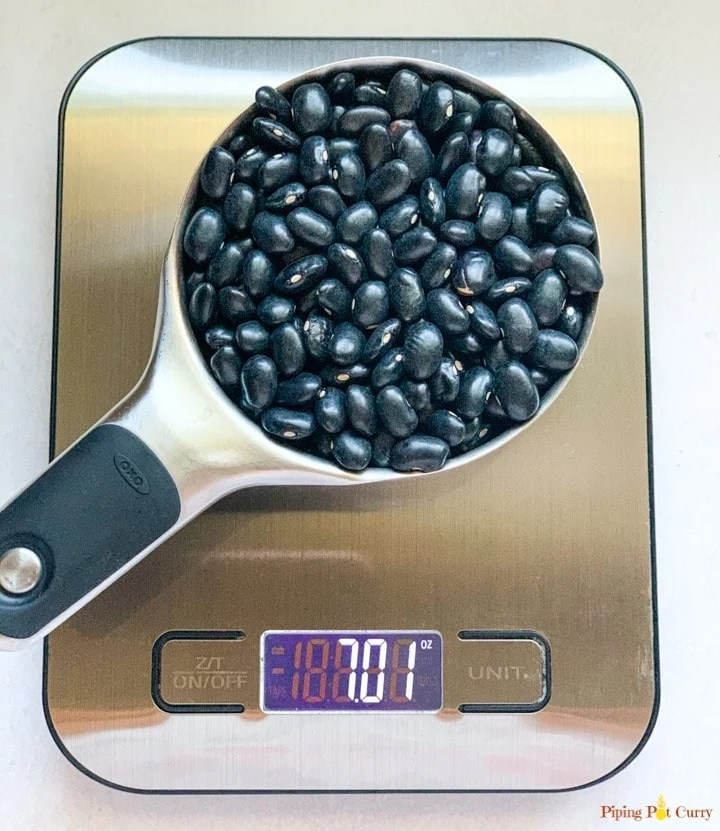 black beans in a measuring cup on a metal food scale