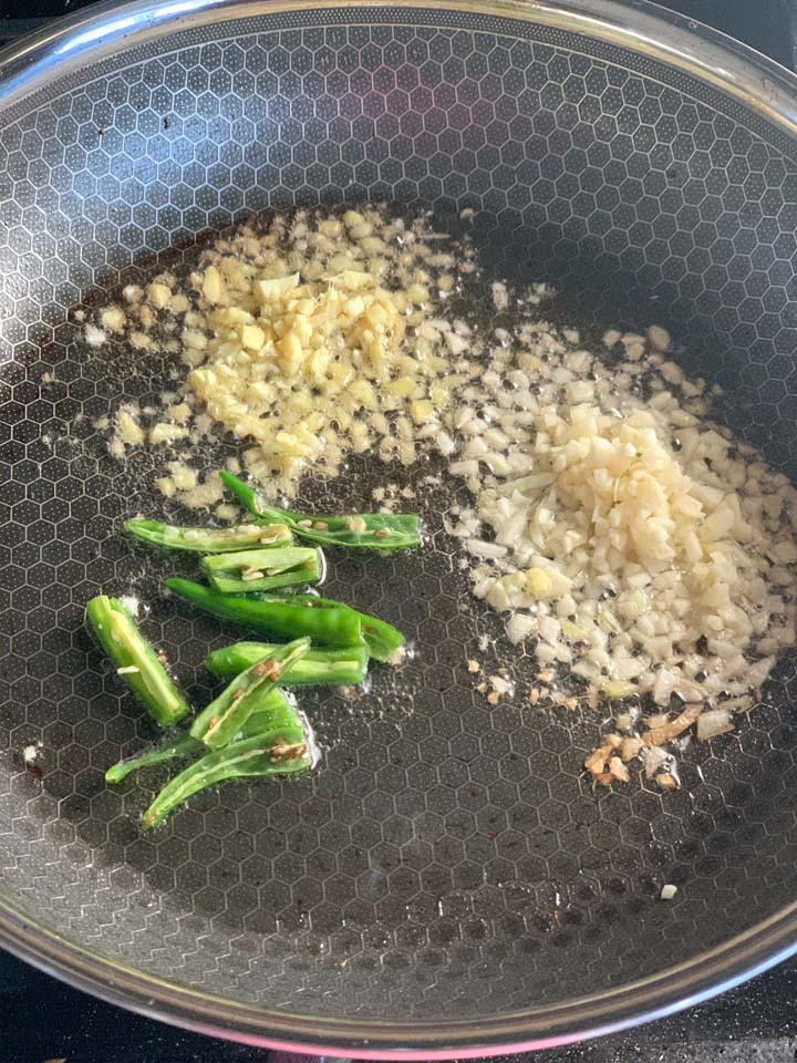 Green chili, ginger and garlic in oil in a pan