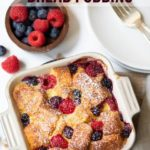 Air Fryer Berry Bread Pudding in a baking pan with fresh berries on the side