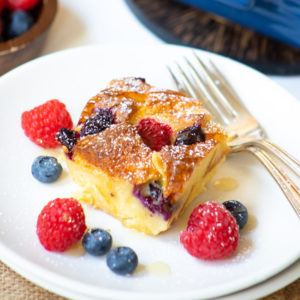 Berry Bread pudding served in a white plate with fresh berries on the side