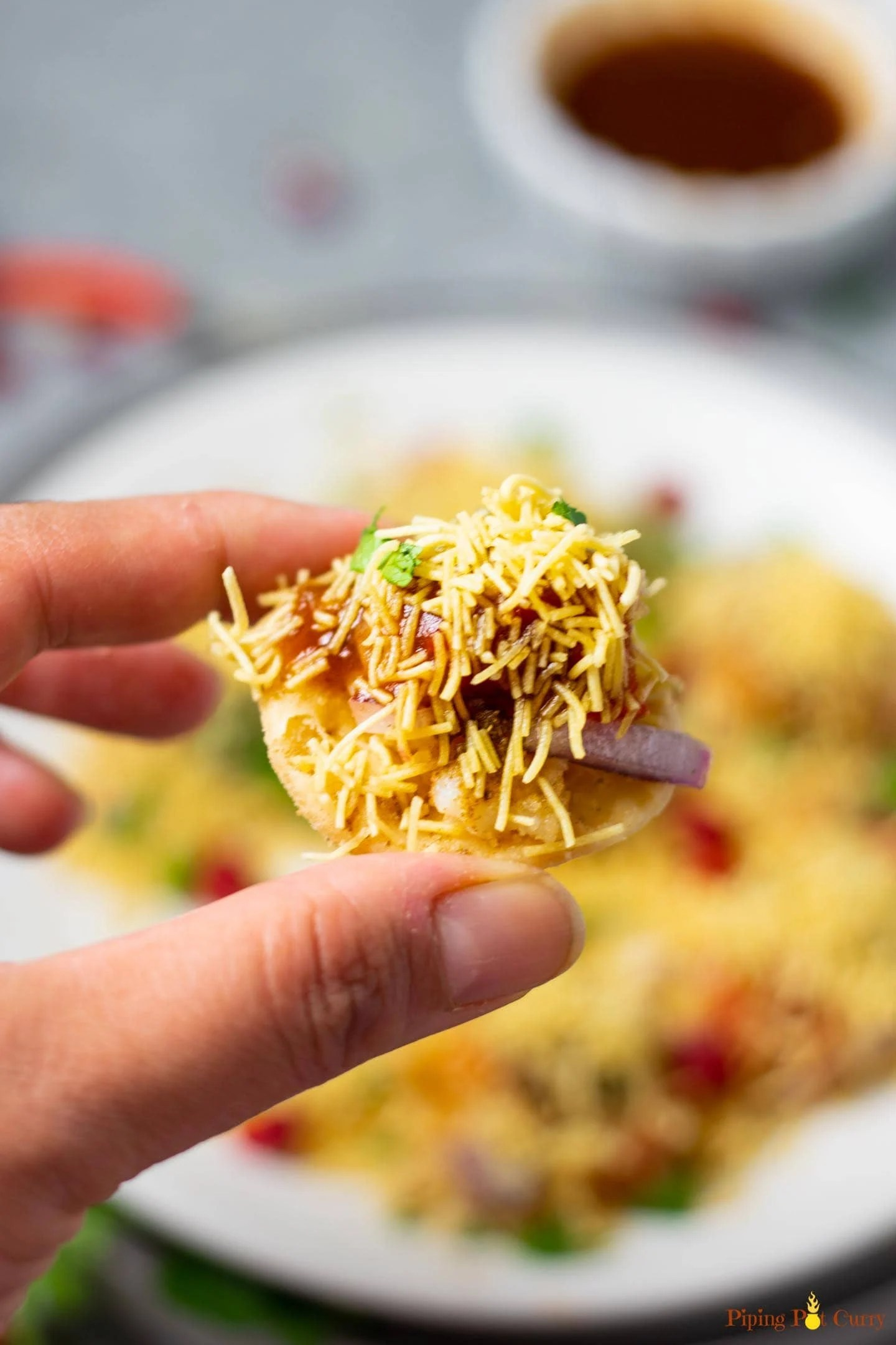 Closeup of a sev puri with a whole filled plate in the background