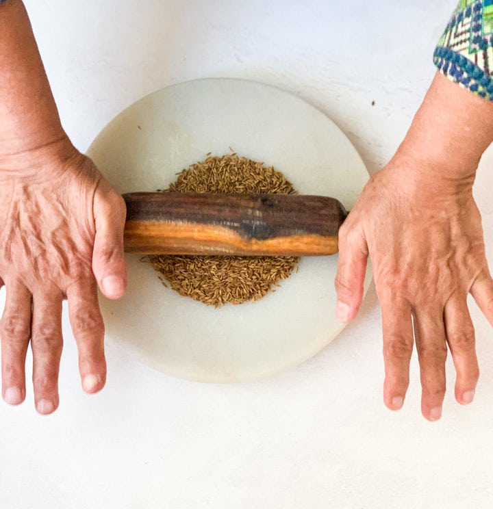 Start rolling roasted jeera with rolling pin