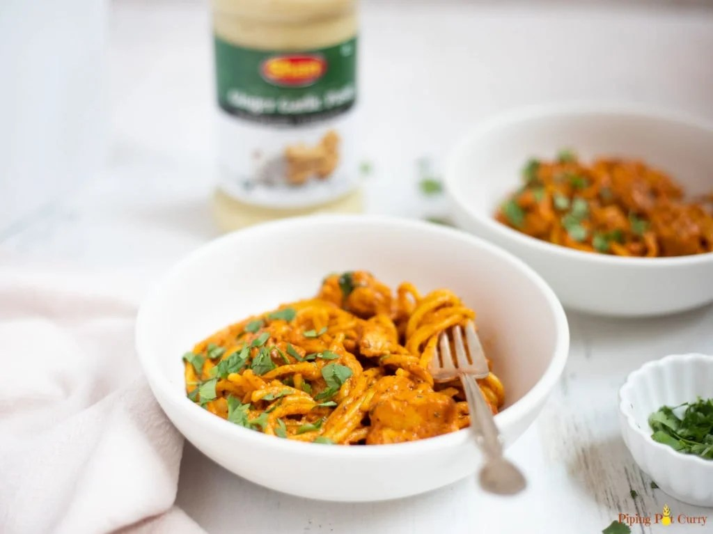 Creamy tikka masala pasta in 2 white bowls with cilantro and a bottle in the background