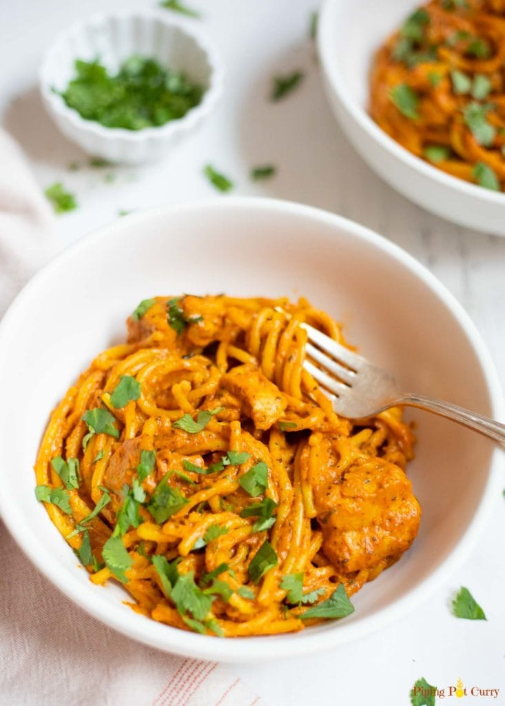 indian style spaghetti with chicken in white bowls garnished with cilantro