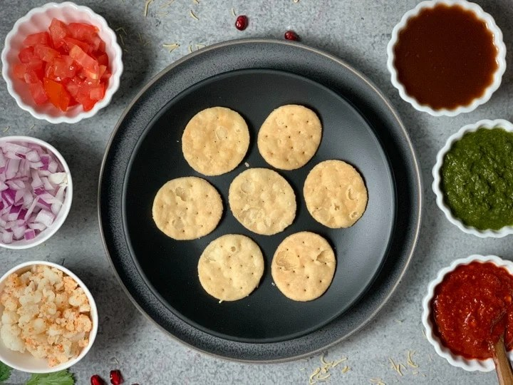 Puri on a plate with onions, potato, tomato and chutneys around it.
