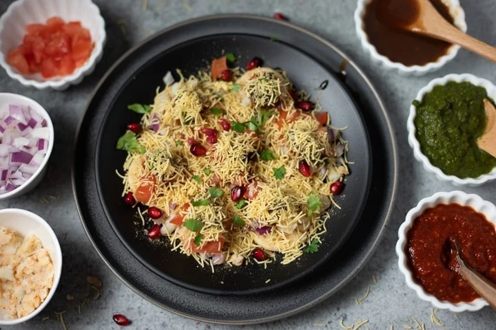 Sev puri garnished with pomegranate and cilantro in a black plate.
