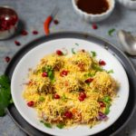 Sev puri street chaat in a white plate with chutneys spread around