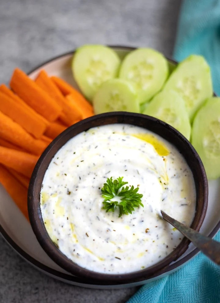 yogurt dip garnishes with parsley in a bowl along with carrots and cucumbers on the side to dip