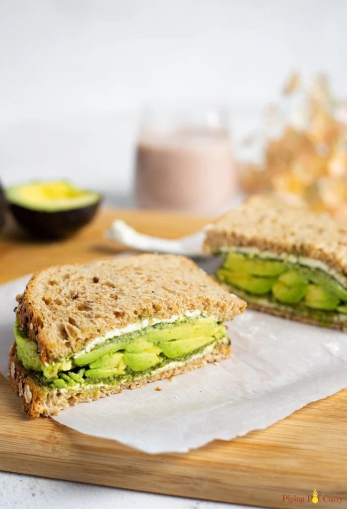 Avocado sandwich on a cutting board with a smoothie in the back