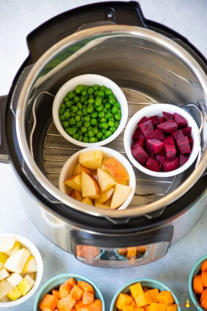 Ramekins with diced veggies in the instant pot on a steamer basket