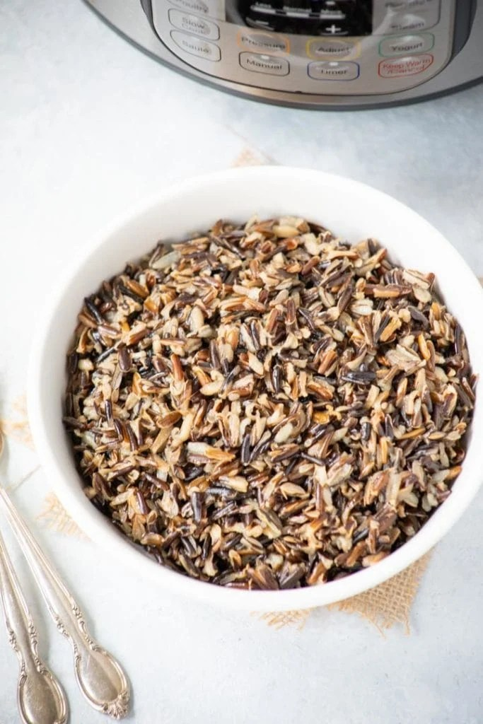A bowl of cooked wild rice in front of the instant pot