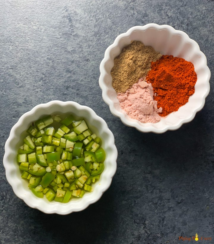 Green chili in vinegar in a bowl and spices in another small white bowl