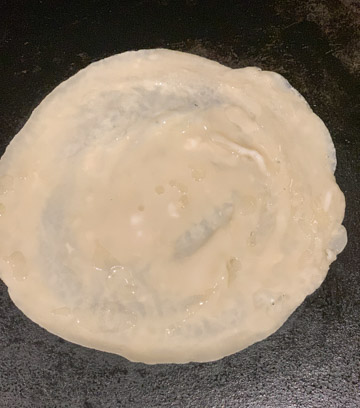 Batter spread to make a flatbread on a Tawa