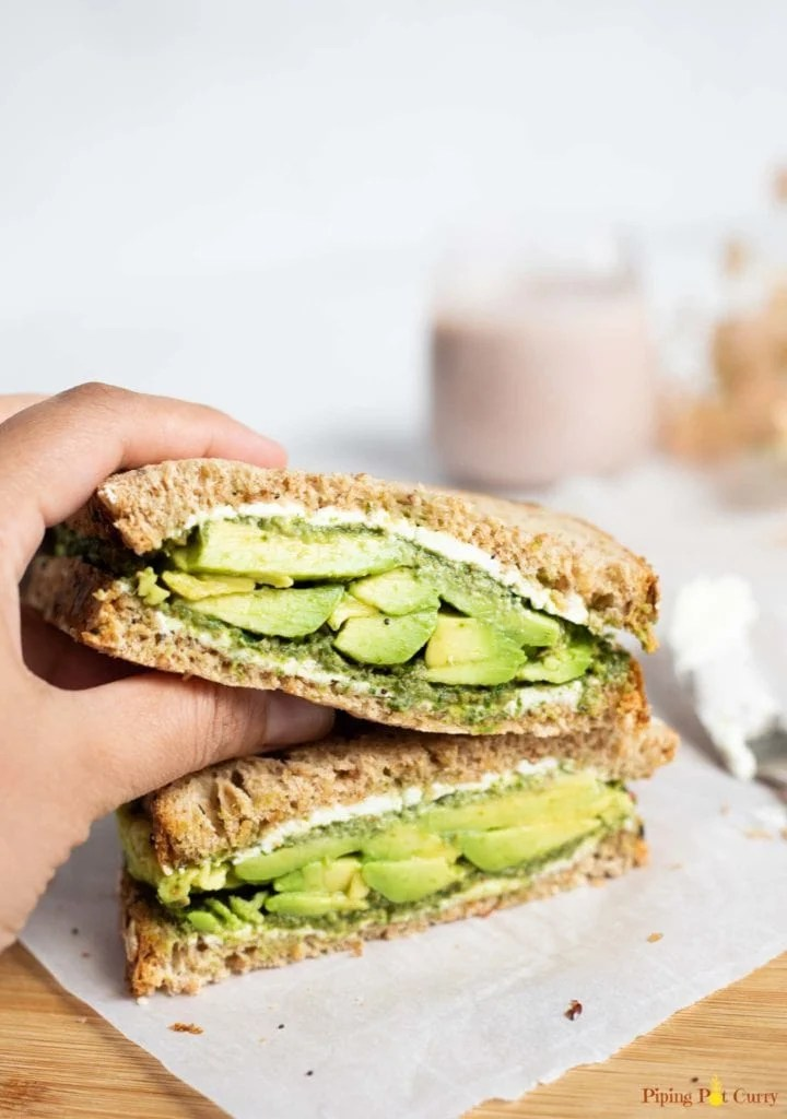 Sandwich with avocado, chutney and cream cheese being picked to be eaten