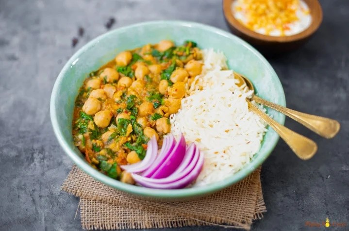 spinach chickpea curry along with rice in a pretty bowl