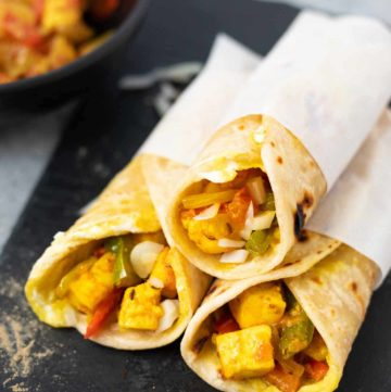 Three paneer Kathi roll wraps on a black base with a bowl of the filling in the back