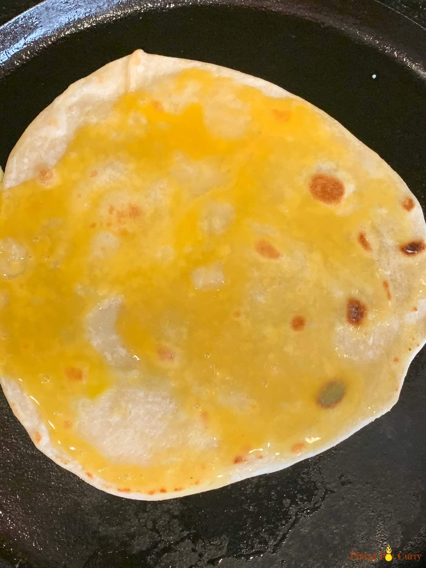 Egg spread on one side of a flatbread on a pan