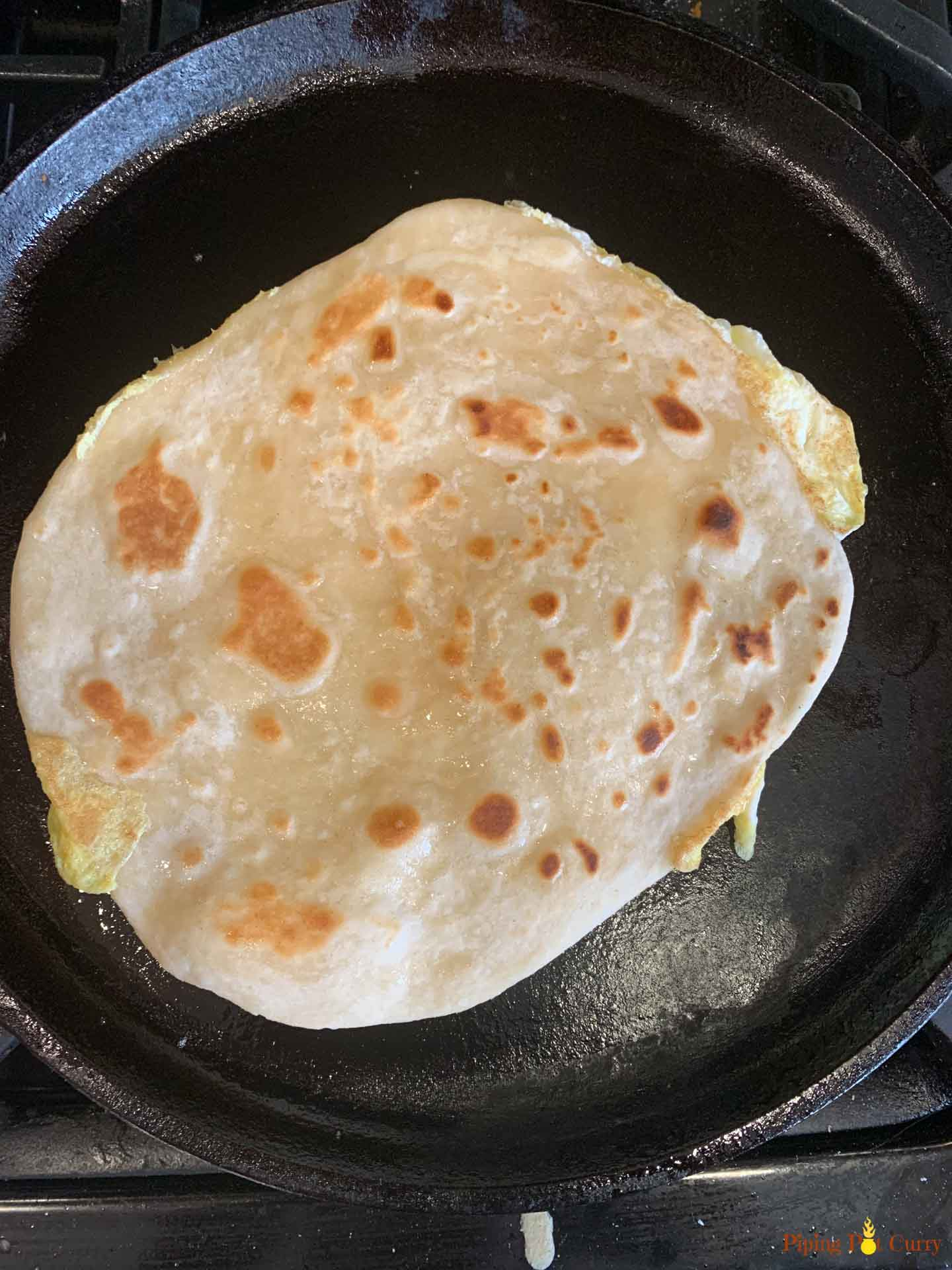 A flatbread being cooked on a pan