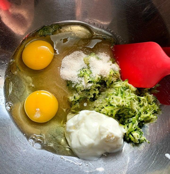 Zucchini, eggs, yogurt, sugar in a bowl