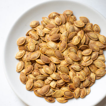 Roasted pumpkin seeds in a white plate