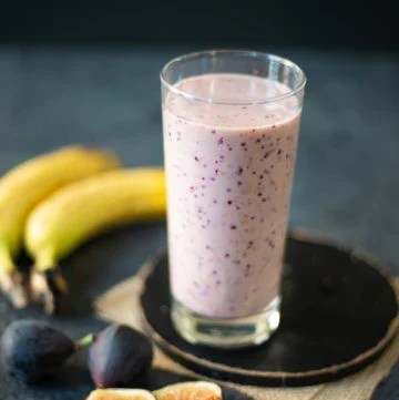 Banana Fig Smoothie in a glass with the ingredients around the glass