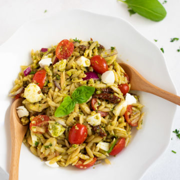 Pesto orzo pasta salad with tomatoes and mozzarella garnished with basil leaves