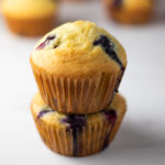 2 blueberry muffins stacked up with a few in the back