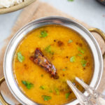 Dal (lentil soup) in a bowl with a red chili tadka and rice on the side