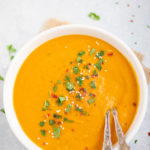 Creamy Carrot Soup garnishes with cilantro, red pepper flakes and sesame seeds