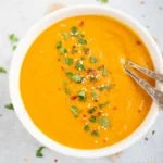 Creamy Carrot Soup in a white bowl garnishes with cilantro, red pepper flakes and sesame seeds