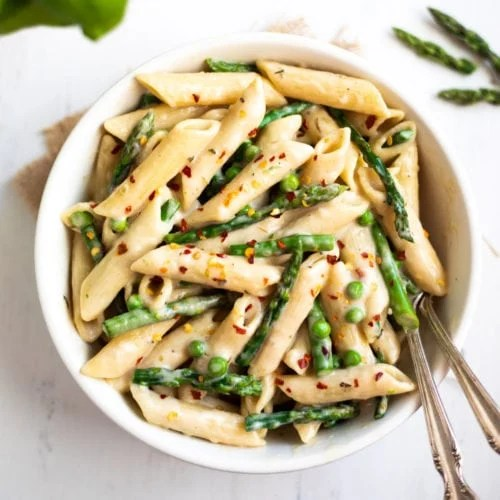 Penne Pasta with green Asparagus and peas in a white bowl