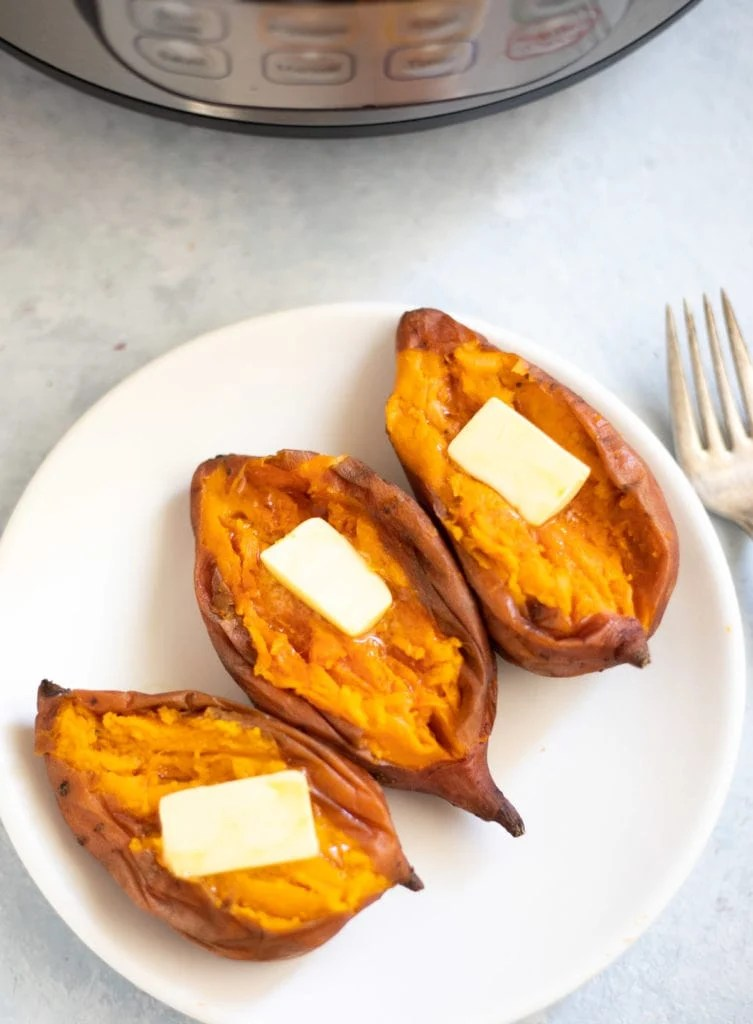 Creamy Sweet potatoes topped with butter in a white plate ion front of the instant pot