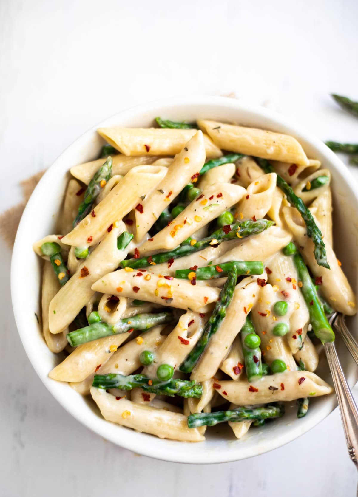 spring looking green asparagus and peas pasta in a bowl
